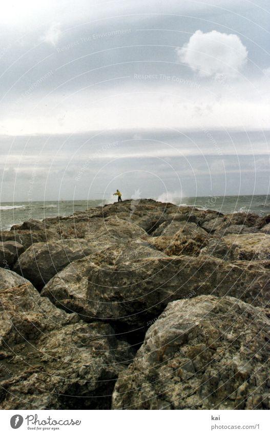 EinsamerAngler Natur Meer Einsamkeit Ferne Sturm Frankreich Fernweh Gischt Felsspalten Gesteinsformationen Hochformat Felsküste