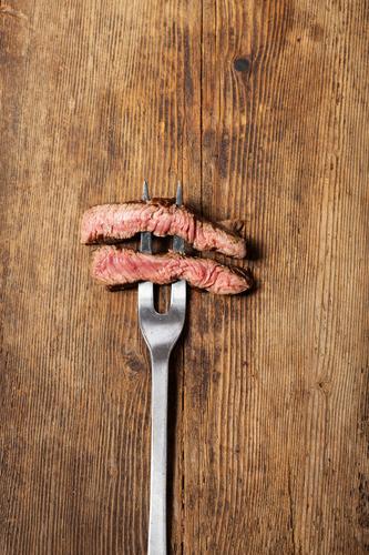 Steakgabel Lebensmittel Fleisch Essen Abendessen Gabel Billig gut braun silber Ehrlichkeit Rindersteak medium Fleischgabel rustikal Holzbrett Holztisch Scheibe