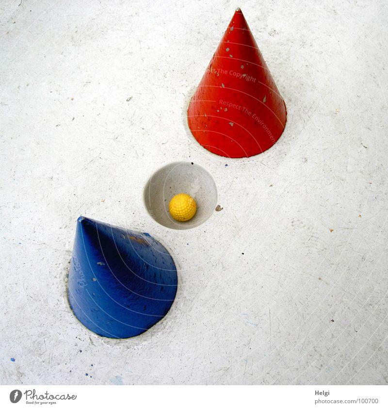 gelber Minigolfball liegt in einem Loch auf einer grauen Minigolfbahn mit rotem und blauem Kegel Golfball schwierig zielen schlagen Sportveranstaltung Spielen