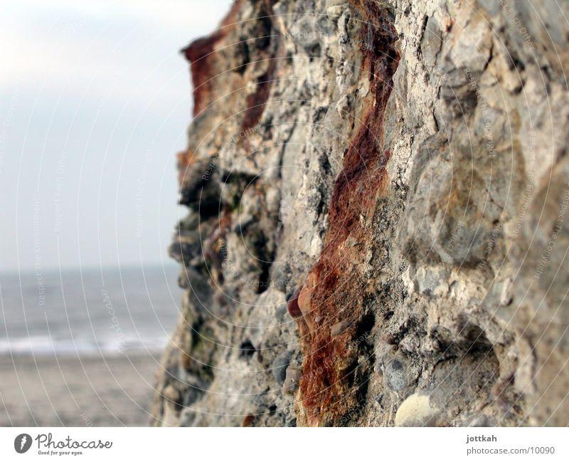 Am Bunker vorbei alt Wasser Meer Strand Wand Stein Sand Beton kaputt Rost Material Oberfläche rau hart zerbröckelt