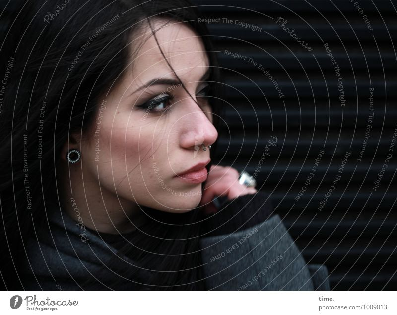. feminin Junge Frau Jugendliche 1 Mensch Mauer Wand Mantel Piercing schwarzhaarig langhaarig beobachten drehen Blick dunkel schön Gefühle Wachsamkeit Vorsicht