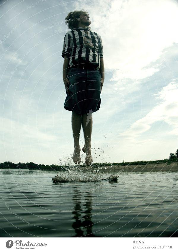wassergeburt Himmel Mann Wasser Strand Freude Wolken Spielen springen Wellen fliegen hoch Wassertropfen Junger Mann aufwärts Dynamik Wasseroberfläche