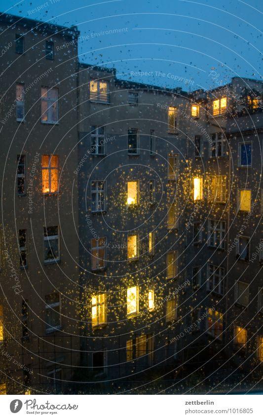 Regen am Abend dunkel Fenster Haus Herbst hinterhaus Regenwasser Häusliches Leben Wohnhaus Wohngebiet Mehrfamilienhaus Vorderseite Fensterfront erleuchten Licht