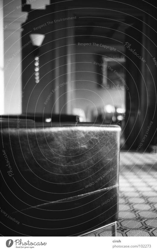 launsch Hotel Sessel Ledersessel schwarz Sofa einfach Lampe Möbel Unschärfe Detailaufnahme Schwarzweißfoto alt modern fliesenboden Foyer jahrhundertwende