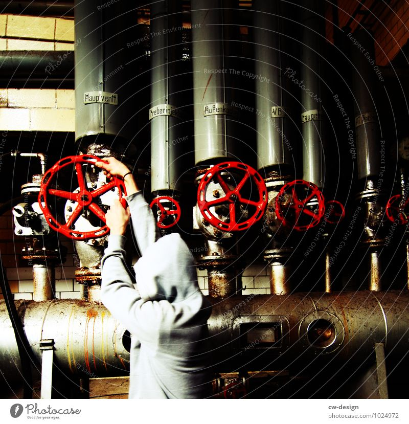 junger Mann schließt Ventil im Heizkraftwerk Industrie Industrieanlage heizungsinstallateur Heizungspumpe Heizungstechnik Heizungskeller Farbfoto öffnen