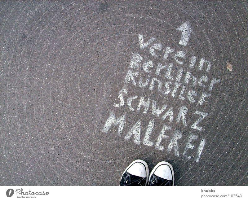 Schwarzmaler Beton Schuhe Schablone weiß grau Text spontan Richtung Club Verbote Verkehrswege Buchstaben Schriftzeichen Kunst Kultur Pfeil Graffiti Fund Verein