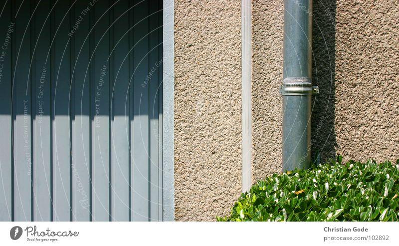 Garage, Mauer, Rohr und Busch Garagentor Einfahrt Gärtner Sträucher Fallrohr Schatten blau grün rot KFZ Einfamilienhaus Häusliches Leben Vorgarten Reihenhaus