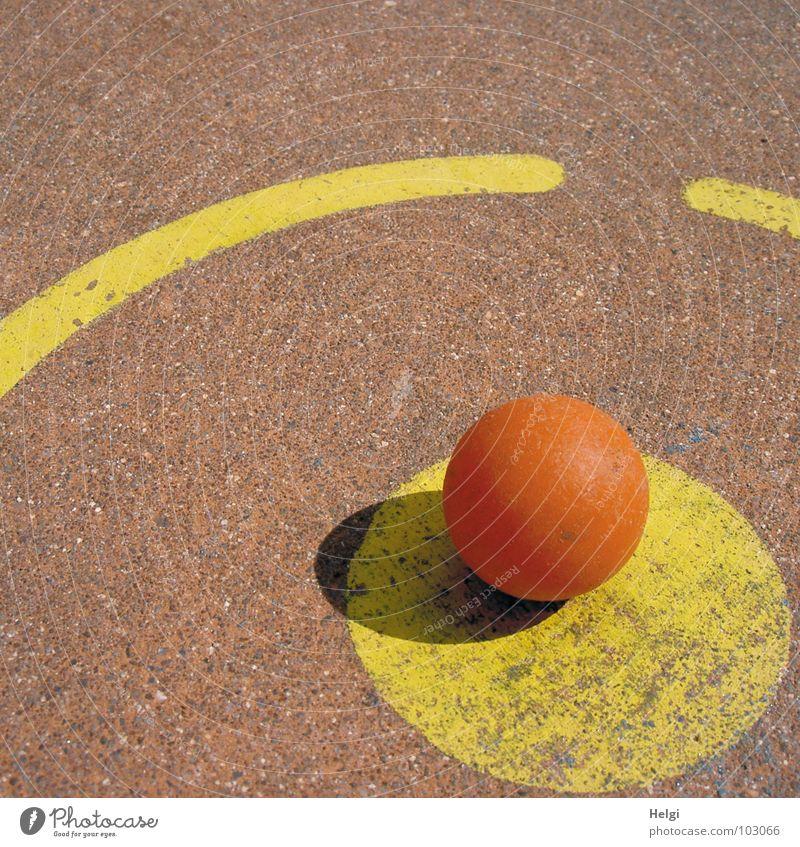 orangefarbiger Minigolfball liegt am Abschlagpunkt auf einer Minigolfbahn rund schlagen Spielen Sportveranstaltung gelb rot Beton angemalt verlieren