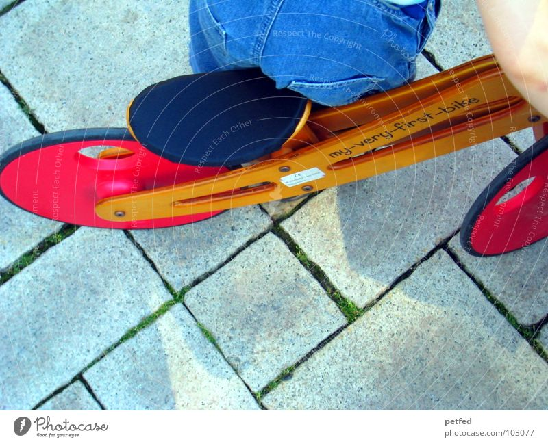 MY-VERY-FIRST-BIKE Mensch Kind blau rot Freude Spielen Stein braun Fahrrad Arme klein laufen Geschwindigkeit Jeanshose fahren stehen