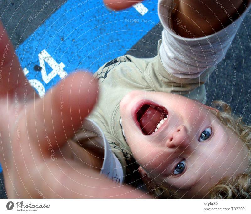Lebensfreude Kind blond Grimasse Finger T-Shirt Asphalt Vogelperspektive Gesicht Haare & Frisuren Blick lustig Freude Mund Verkehrswege Schilder & Markierungen