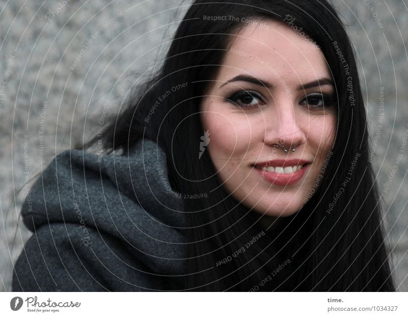 . feminin 1 Mensch Mauer Wand Mantel Piercing schwarzhaarig langhaarig beobachten Lächeln lachen Blick warten elegant schön Fröhlichkeit Zufriedenheit
