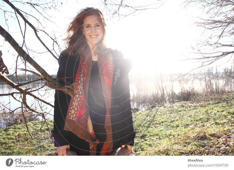 draussen Stil Ausflug Freiheit Junge Frau Jugendliche Grübchen 18-30 Jahre Erwachsene Natur Landschaft Herbst Schönes Wetter Baum Gras Sträucher Seeufer Mantel