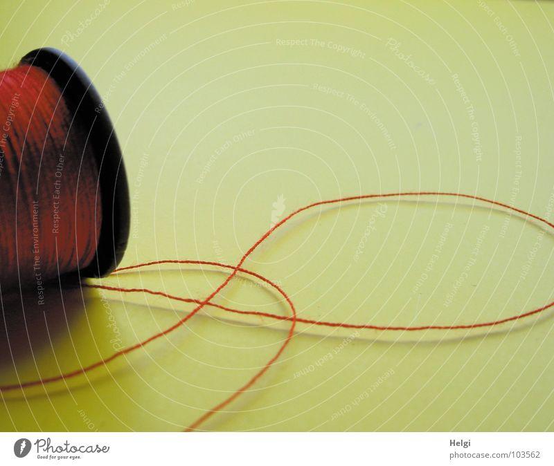 roter Faden an einer Garnrolle auf gelbem Hintergrund Nähgarn Rolle Nähen Naht binden festbinden Faden verlieren Schneider heften rollen Nähmaschine schwarz