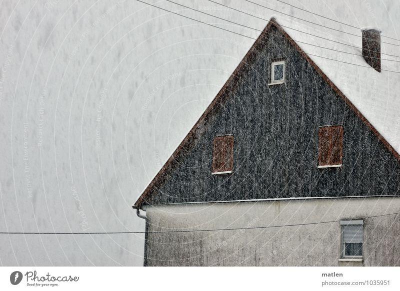 Schafskälte Dorf Menschenleer Haus Mauer Wand Fassade Fenster Dach Schornstein dunkel braun grau weiß Schneefall Telefonleitung Rollladen Architektur Farbfoto