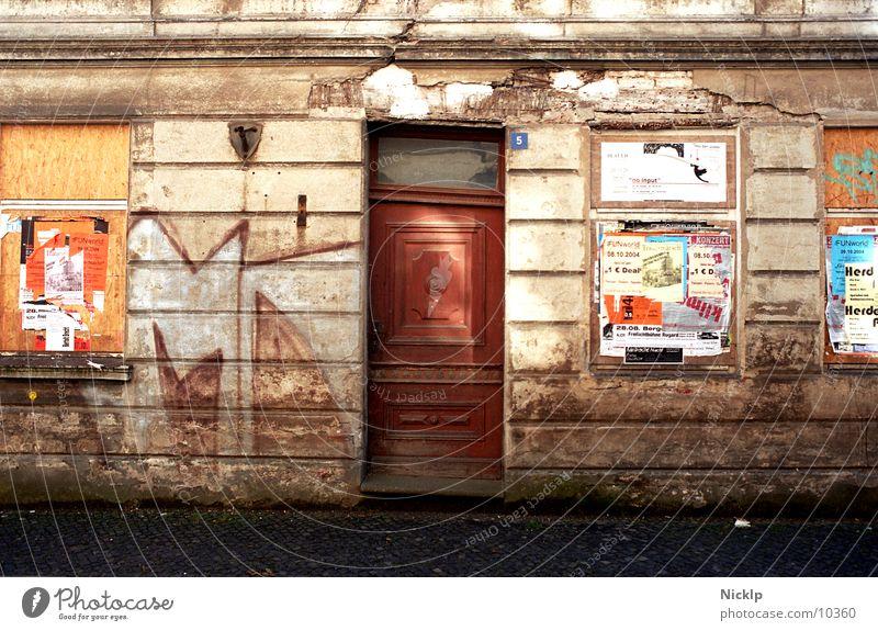 schiefer Haussegen mal anders alt Haus Fenster Wand Graffiti Herbst Mauer Zeit Fassade dreckig Tür Vergänglichkeit Schönes Wetter Kultur Abenteuer kaputt