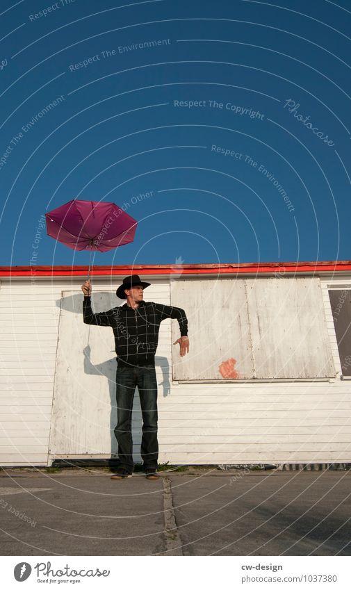 Mann mit Schirm Mensch maskulin Jugendliche Leben 1 18-30 Jahre Erwachsene 30-45 Jahre Dorf Haus Hütte Ferienhaus Fassade festhalten Blick stehen