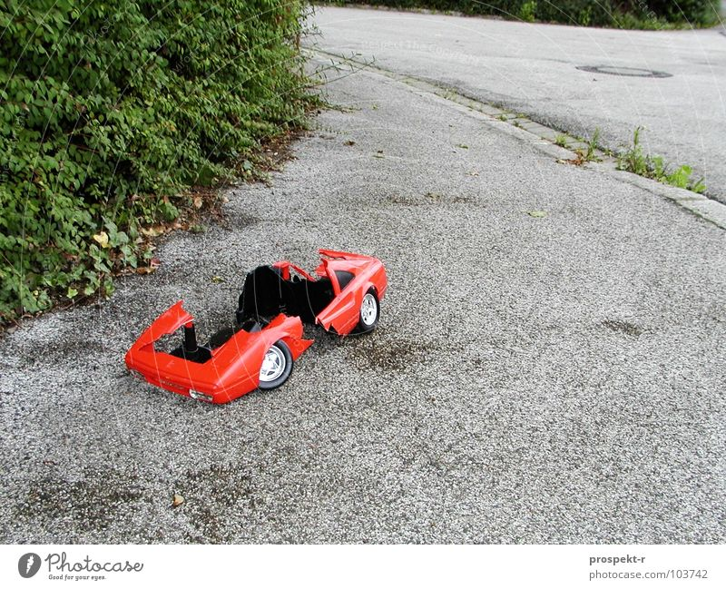 Broken Dreams grün Pflanze rot Straße grau PKW kaputt Spielzeug Kindheit Kurve Zerstörung Gully Bordsteinkante Chrom