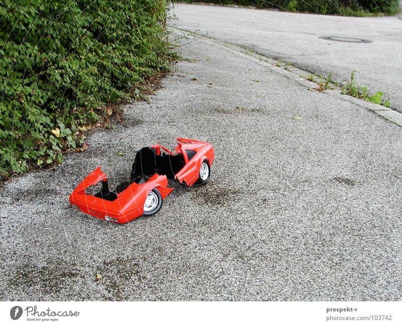 Broken Dreams kaputt Gully Spielzeug rot grau grün Zerstörung Bordsteinkante Chrom PKW Straße gehsteig Ferrari Kurve kleine Welt Pflanze Chromfelgen prospekt-r