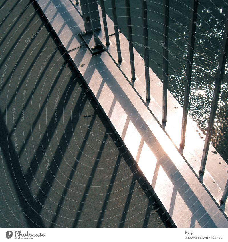 Licht und Schatten glänzend Geometrie dünn Ecke Sonnenlicht Gegenlicht Brücke Sommer Fluss Bach Geländer Stab Metall kahl Wasser Linie hoch verrückt Reflektion