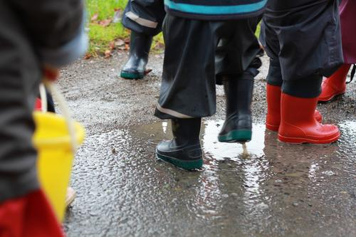Spaß im Regen Freude Spielen Kindergarten Mensch Kleinkind Kindheit Leben Beine Kindergruppe 1-3 Jahre Wasser Herbst schlechtes Wetter Dorf Regenhose