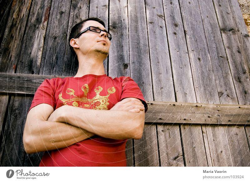 Niveau sieht nur von unten aus wie Arroganz Hochmut rot T-Shirt ruhig abweisend Mann maskulin Froschperspektive Brille Brillenträger Tor Holz Holztür Holztor