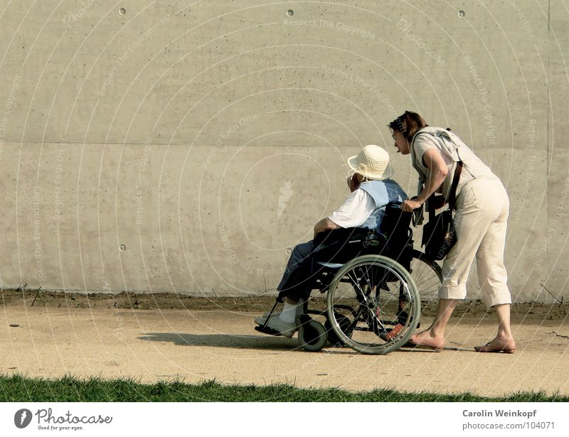 Psst, hast du den da gesehen? sprechen Mensch Frau Erwachsene Senior Küste Wege & Pfade Hut Bewegung gehen Mitgefühl Hilfsbereitschaft Rollstuhl Spaziergang