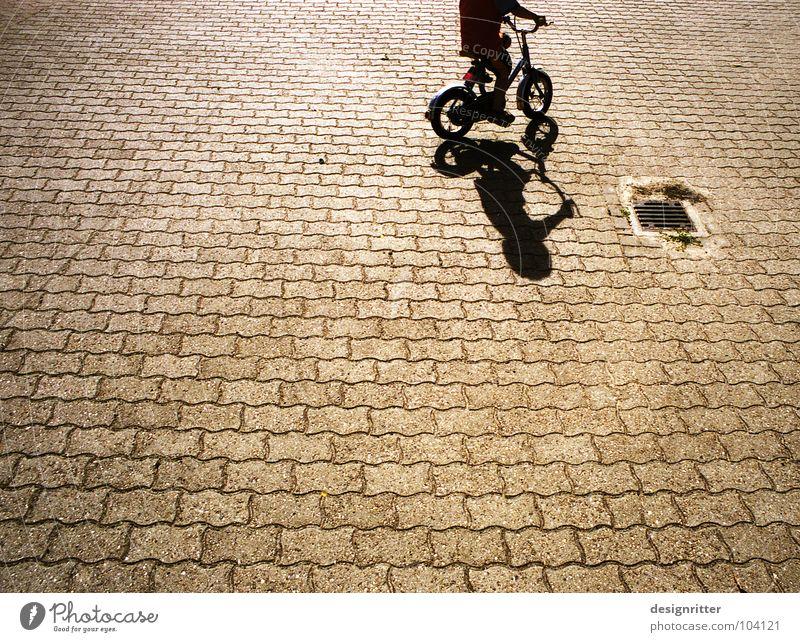 Trial and ... Fahrrad fahren Fahrradfahren Kinderfahrrad Kopfsteinpflaster Fußgängerzone üben Beginn Spielen Rad Schatten Junge Straße Wege & Pfade Stein