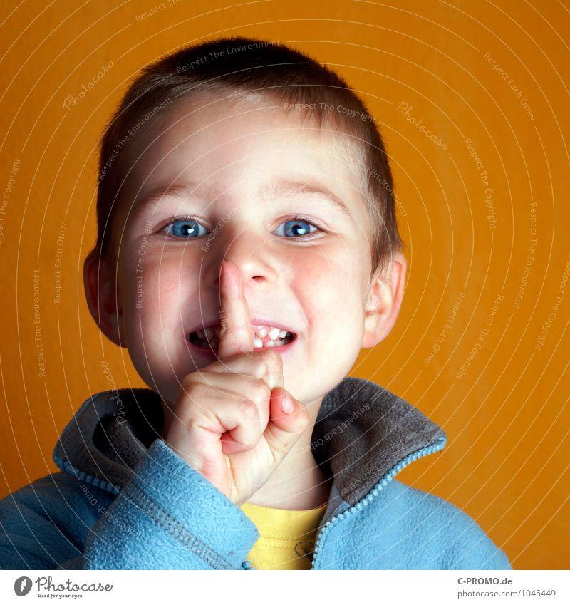 Junge mit strahlenden Augen hält Finger vor Mund Kind Kopf 1 Mensch 1-3 Jahre Kleinkind 3-8 Jahre Kindheit Pullover blau gelb Verschwiegenheit diszipliniert