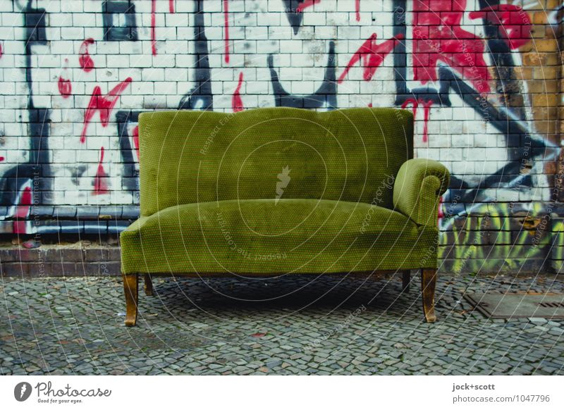 Unvollständiges Sofa steht  auf dem Bürgersteig Subkultur Straßenkunst Kreuzberg Mauer Backstein Graffiti Pfeil kaputt retro grün Unbekümmertheit Sperrmüll
