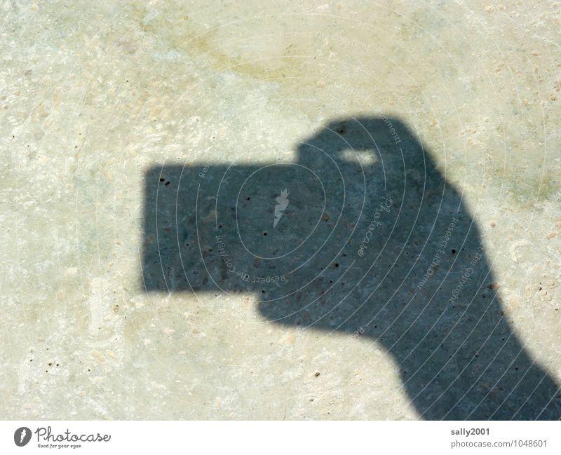 Knips... Fotokamera Hand Finger klein Fotografieren Auslöser Steinboden Schattenspiel festhalten Silhouette eckig Farbfoto Außenaufnahme Menschenleer Tag