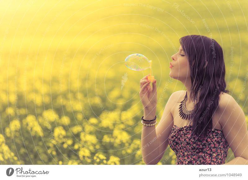 Beautiful woman blowing one soap bubble in yellow summer meadow Mensch Frau Natur schön Sommer Junge Frau Erholung Blume ruhig Freude Umwelt Erwachsene Leben