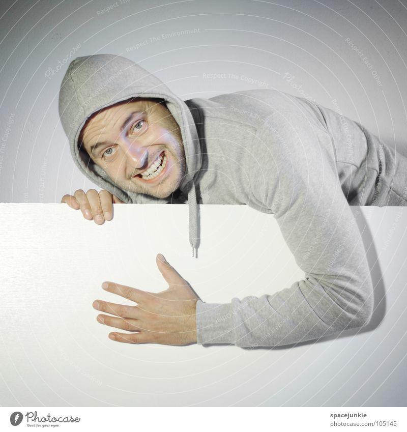 Du freust dich ja gar nicht Mann Porträt lustig Humor skurril Überraschung Mogelpackung sinnlos Pullover Wand weiß Wahnsinn verrückt Freude Versteck