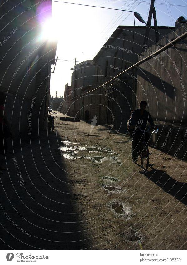 Pfützen Gegenlicht Reflexion & Spiegelung Fahrrad Usbekistan Buchara Asien Gasse Dorf Außenaufnahme Verkehrswege Wasser Mensch veträumt Tradition Sonne