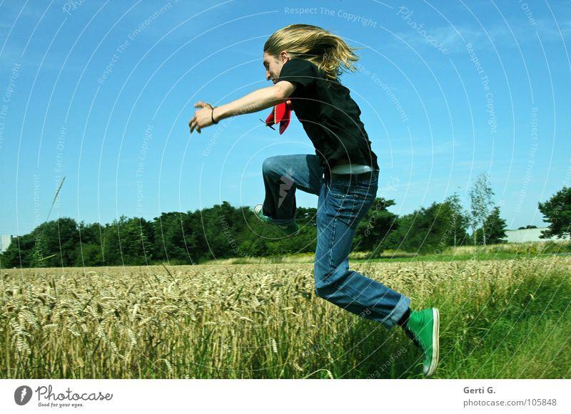 springtime Mann langhaarig blond jeansblau Chucks grün T-Shirt schwarz Feld Weizen Weizenfeld springen Kornfeld Am Rand Gras Halm Ähren reif Modellflugzeug Baum