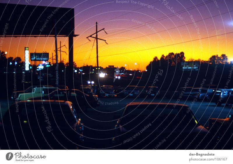 irgendwo in Missouri, westwärts dunkel Gegenlicht Sonnenuntergang Amerika Parkplatz Pause Nacht Flutlicht Werbeschild Mobilität Nachtleben Verkehr violett