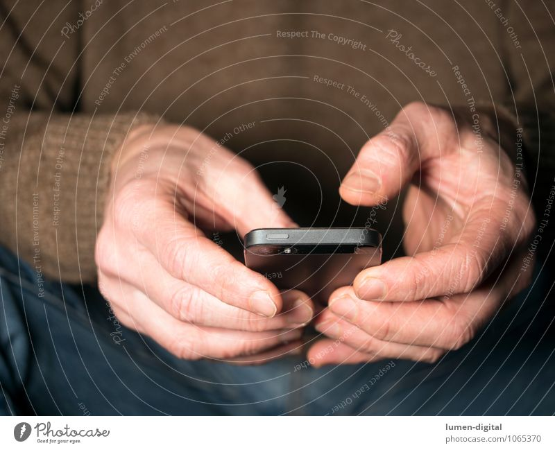 Hände mit Smartphone Handy PDA Finger Kommunizieren sitzen Telefongespräch Chatten clipping device electronic hands holding jeans man sitting sweater tap touch