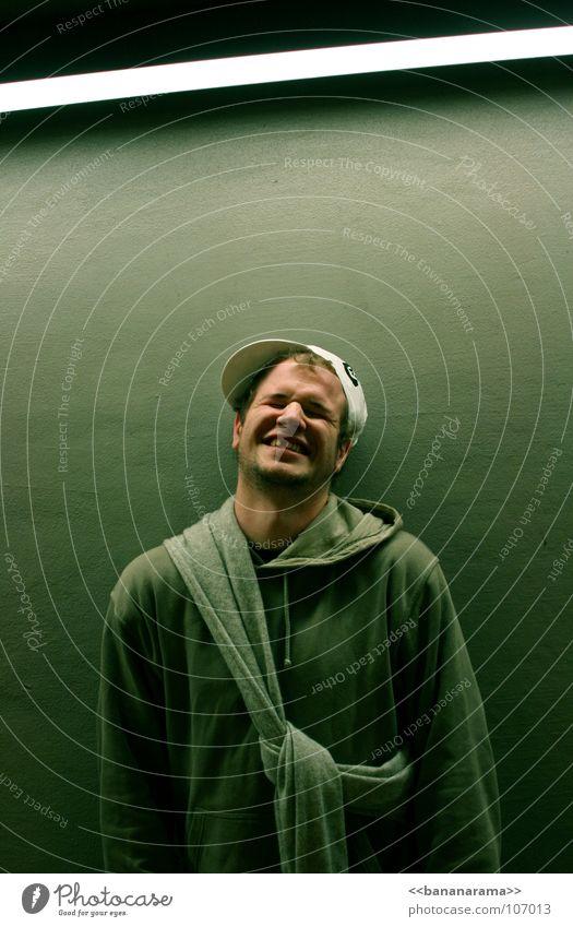 Ein ganz spezielles Lächeln grinsen Humor lachen Pullover Mütze Baseballmütze Lampe Neonlicht Licht Wand kraus grün Parkhaus Gefühle Stil Mann Zahnlücke lustig