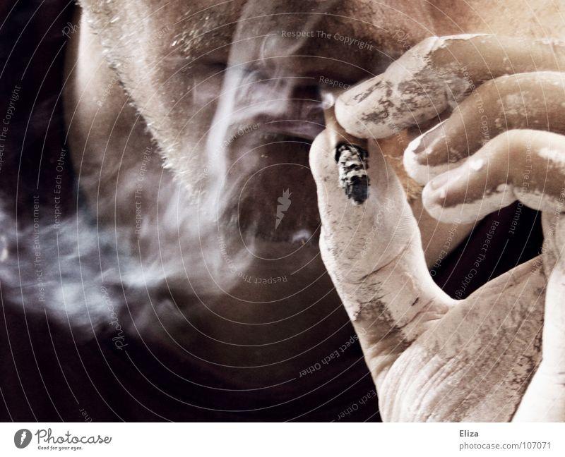 Mann mit Drei-Tage-Bart und weißer Hand von Malerfarbe raucht eine Zigarette und bläst Rauch aus rauchen Zigarettenstummel ungesund Nikotin ekelig ekelhaft