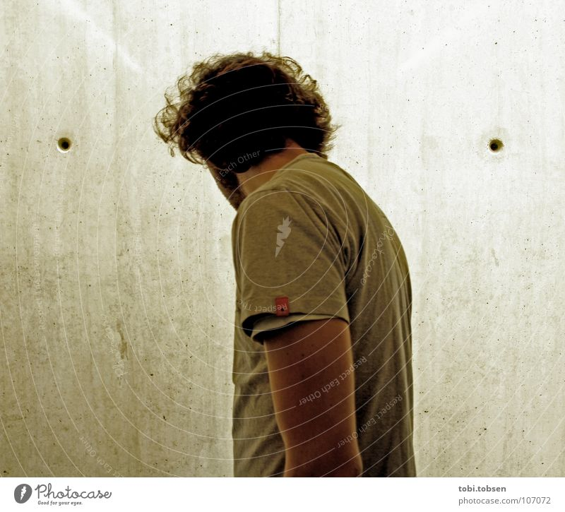 Mann vor Wand mit zwei Löchern Oberlicht Beton Erkenntnis gehorsam böse schwarz grau geheimnisvoll Loch T-Shirt Einbahnstraße Fahrstuhl Schacht Konzentration