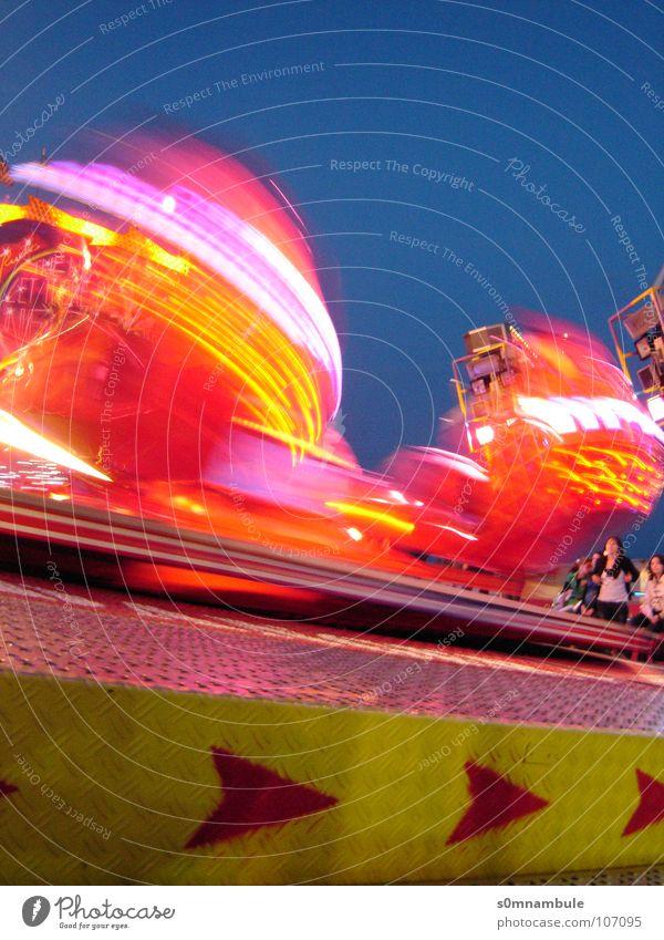Rummel bei Nacht drehen Geschwindigkeit rot gelb Euphorie Jahrmarkt Licht Fahrgeschäfte Richtung Schwindelgefühl Langzeitbelichtung Freude Oktoberfest