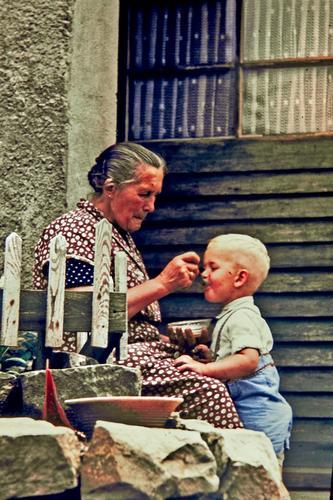"""Zeitreise """"Ein Haps für Oma"""" Mensch Kind blau grün Liebe Senior Junge grau Essen Stein Tür blond Kindheit lecker Dorf Hemd"""