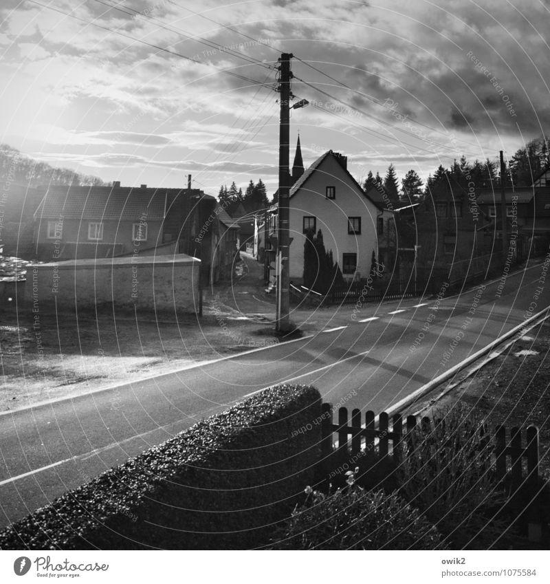 Dorf im Südharz Himmel Wolken Baum Sträucher Hecke Vorgarten Zaun bevölkert Haus Kirche Gebäude Kirchturmspitze Mauer Wand Fenster Straße Mittelstreifen