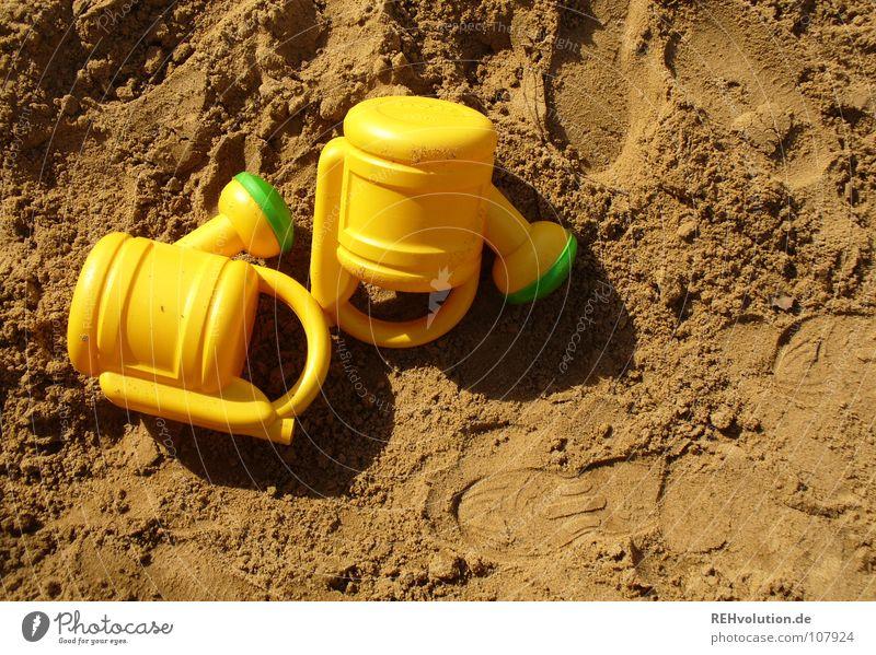 Sandkastenbefeuchtungszwillinge Zwilling identisch Spielen gelb grün Fußspur braun erdig Sommer 2 toben Freude liegen liegen gelassen gleich Gieskanne