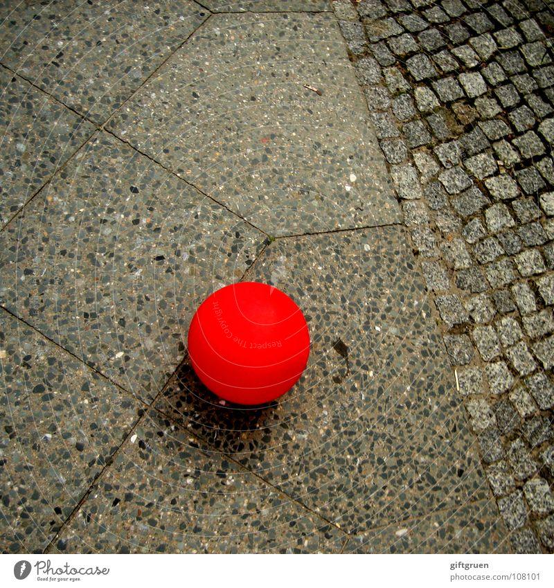 liegengeblieben rot Straße Farbe grau Stein Luft fliegen Ball Luftballon rund liegen Verkehrswege Kopfsteinpflaster
