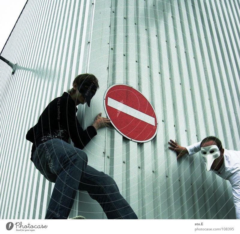 schwarz und weiß Kerl Aktion Maske Schutzmaske Parkplatz Parkhaus Parkdeck Einkaufszentrum Asphalt Haus Gebäude Gelände Wand Richtung Durchgang Verbote Muster