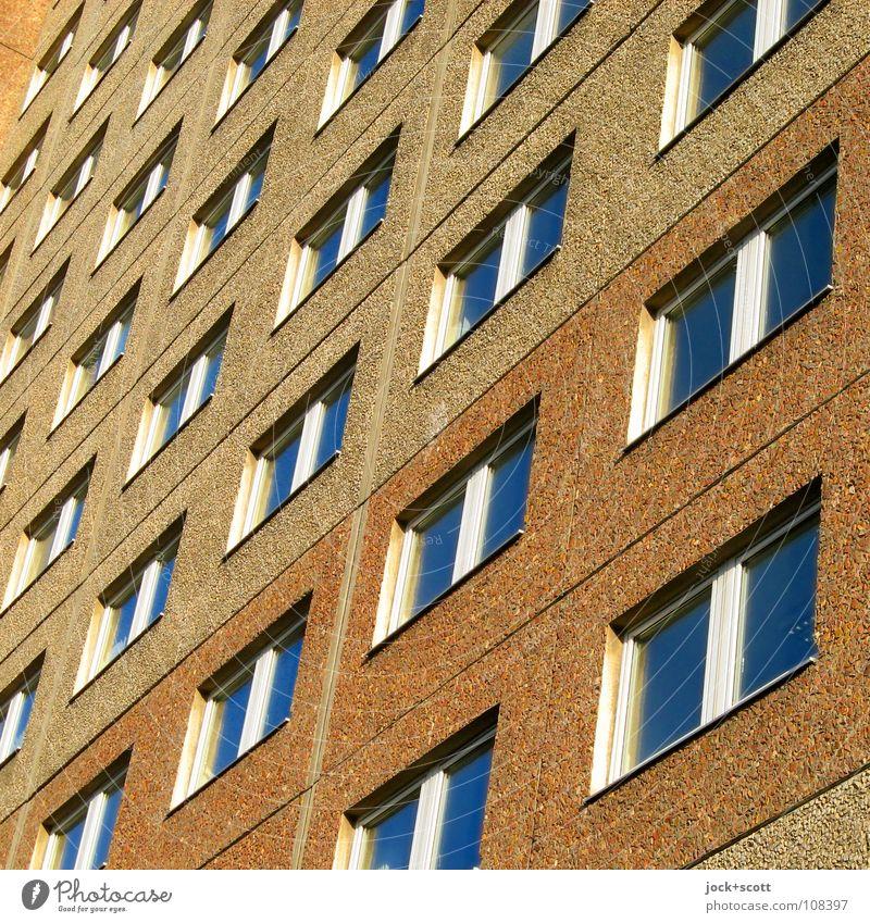 unscheinbare Fassade Architektur Plattenbau Fenster eckig hässlich trist braun Norm Geometrie aufeinander Anordnung DDR diagonal Rechteck Funktionalismus