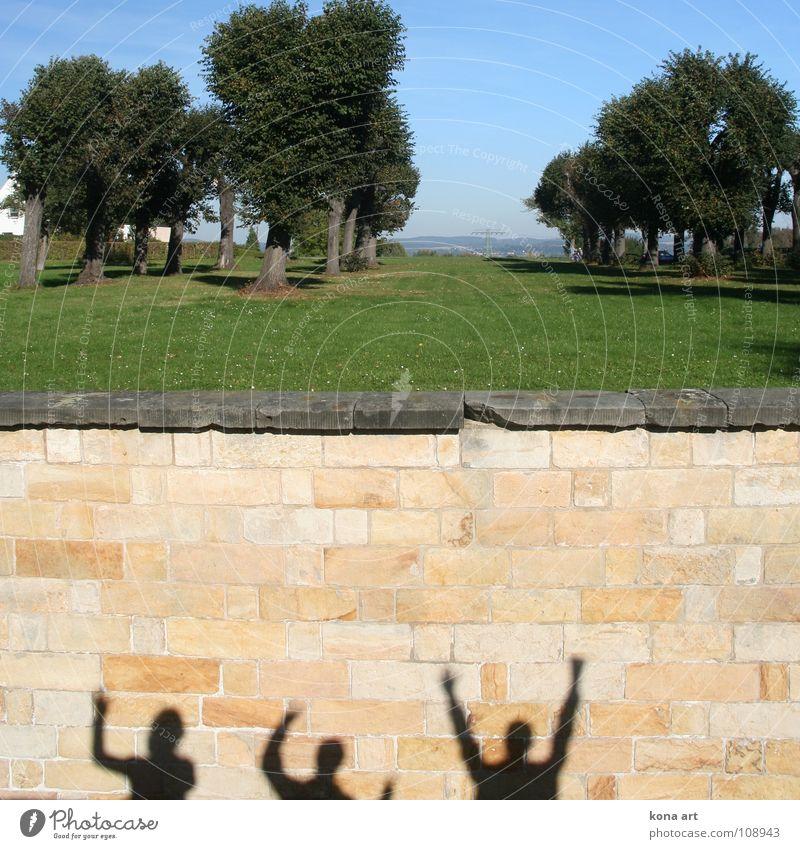 3 finstere Gestalten Mauer Sandstein Mensch winken Baum Aussicht Gruß Freude Menschengruppe Schatten Sonne Sandsteinmauer Arme lustig