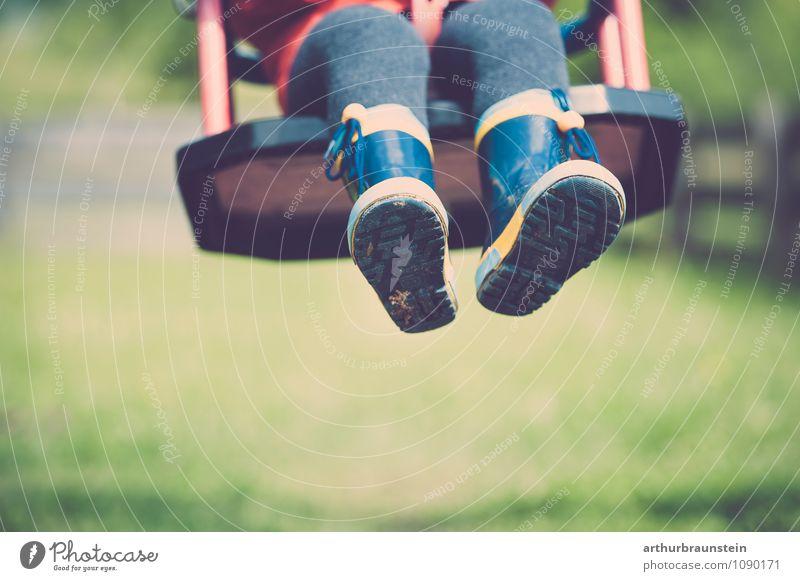Kind schaukelt mit bunten Gummistiefeln Mensch Natur Freude Bewegung Frühling Spielen Glück Garten maskulin Freizeit & Hobby authentisch Kindheit Kleinkind