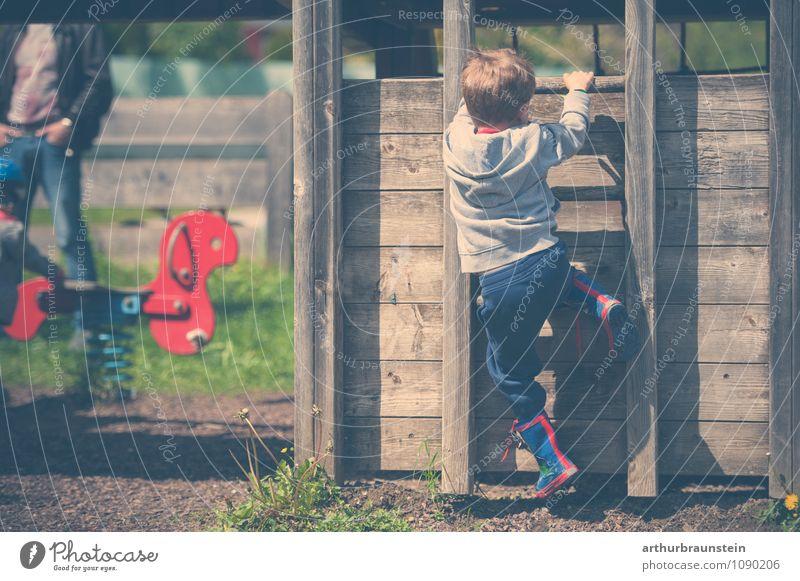 Kind mit bunten Gummisteifel klettert auf Holzhaus am Spielplatz Mensch Natur Mann Freude Erwachsene Bewegung Gras Frühling Spielen Glück Garten Park