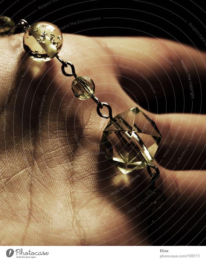 Schmuckstück Hand Glasperle grün schwarz Stimmung Armband Handfläche Finger dunkel schön glänzend schimmern Diamant Reichtum Kette Schatten Linie Beleuchtung